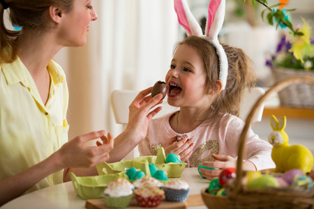 Mother and daughter celebrating Easter, eating chocolate eggs. Happy family holiday. Cute little girl in bunny ears laughing, smiling and having fun. Stok Fotoğraf