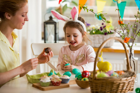 Mother and daughter celebrating Easter, eating chocolate eggs. Happy family holiday. Cute little girl in bunny ears laughing, smiling and having fun. Zdjęcie Seryjne