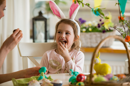 Mother and daughter celebrating Easter, eating chocolate eggs. Happy family holiday. Cute little girl in bunny ears laughing, smiling and having fun. Standard-Bild