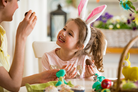 Mother and daughter celebrating Easter, eating chocolate eggs. Happy family holiday. Cute little girl in bunny ears laughing, smiling and having fun. Foto de archivo