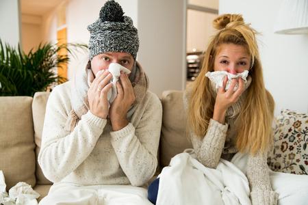 Ziek stel wordt verkouden. Man en vrouw niezen, hoesten, kregen griep, hebben een loopneus. Mensen spuiten medicatie in neus en keel. Stockfoto
