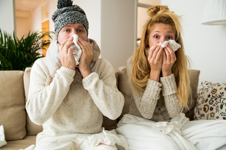 Sick couple catch cold. Man and woman sneezing, coughing, got flu, having runny nose. People spraying medication into nose and throat.