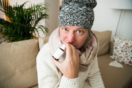 Sick man catch cold. Ill person sneezing, coughing, got flu, having red runny nose, spraying medication. Sitting at home on couch. Stock Photo