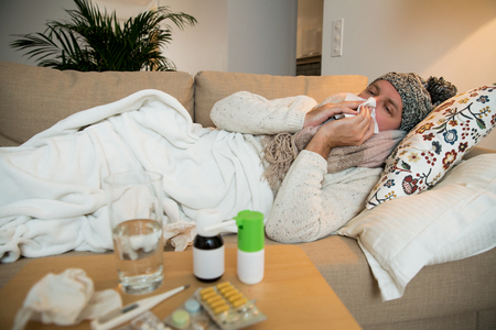 Sick man wearing scarf lying on couch at home under a blanket checking temperature. Living room with table full of medicine and pills. Man with running nose and cough.