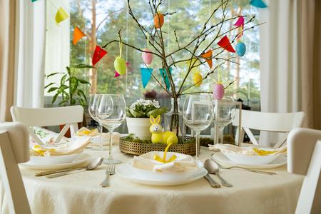 Bellissimo tavolo rotondo servito con decorazioni in sala da pranzo. Coniglietto giallo, rami di salice decorati con colorate uova di Pasqua. Impostazione delle vacanze di primavera Archivio Fotografico - 96930639