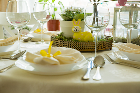 Beautiful served round table with decorations in dining room. Little yellow bunny, willow branches decorated with colorful Easter eggs. Spring holiday setting. Close-up