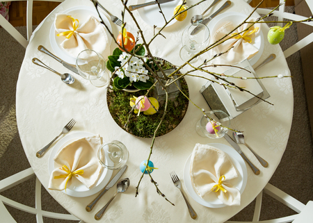 Beautiful served round table with decorations in dining room. Little yellow bunny, willow branches decorated with colorful Easter eggs. Spring holiday setting. Top view shot