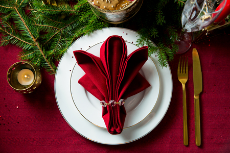 Background of beautiful served table with Red tablecloth and napkins, white china, gold cutlery, spruce tree branches. Top view. Holiday setting, Christmas mood. Stock Photo
