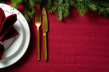 Background of beautiful served table with Red tablecloth and napkins, white china, gold cutlery, spruce tree branches. Top view. Holiday setting, Christmas mood. Stock Photo - 114475917