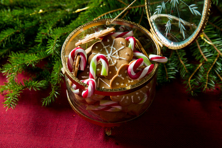Background of gingerbread and candy cane jar and spruce branches on red table cloth. Top view. Christmas mood