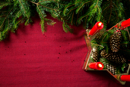 Background of glass and gold candleholder with red candles and spruce branches on red table cloth. Living room decorated with lights and candles and Christmas tree. top view