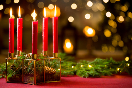 Background of glass and gold candleholder with red candles and spruce branches on red table cloth. Living room decorated with lights and candles and Christmas tree