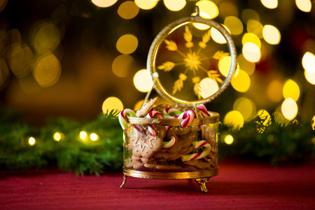 Close-up gingerbread and candy cane jar. Happy family holiday. Living room decorated with lights and candles and Christmas tree. Holiday mood Reklamní fotografie