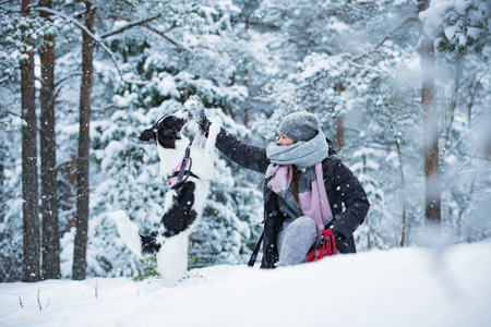Woman playing with dog in snowy forest, enjoying the weather. Running and jumping happy pet, girl laughing, having fun. Beautiful winter landscape with trees in snow.