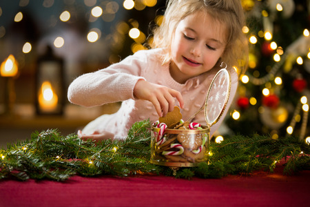 Cute little girl celebrating Christmas, taking candies and gingerbread from glass jar and eating. Happy family holiday. Living room decorated with lights and candles and Christmas tree. Holiday mood