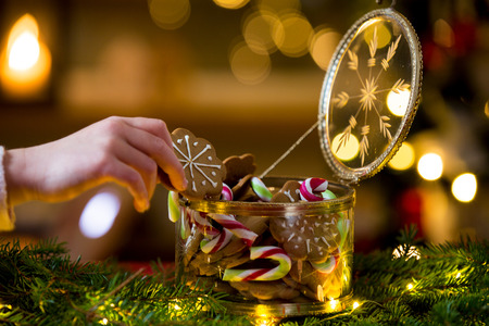 Cute little girl taking candies and gingerbread from glass jar and eating. Happy family holiday. Close-up hand. Living room decorated with lights and candles and Christmas tree. Holiday mood