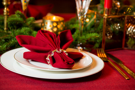 Beautiful served table with candles, Red tablecloth and napkins, white china, gold cutlery, crystal champagne glasses. Holiday setting, close-up plate, Christmas mood.