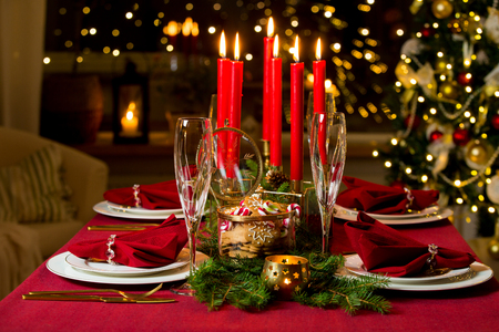 Beautiful served table with candles, Red tablecloth and napkins, white china, gold cutlery, crystal champagne glasses. Living room decorated with lights and Christmas tree. Holiday setting 版權商用圖片
