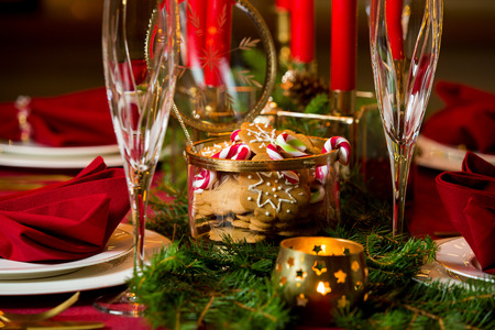 Beautiful served table with candles, Red tablecloth and napkins, white china, gold cutlery, crystal champagne glasses. Holiday setting, close-up gingerbread and candy cane jar, Christmas mood. Reklamní fotografie