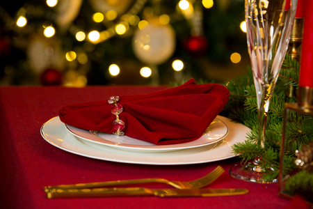 Beautiful served table with candles, Red tablecloth and napkins, white china, gold cutlery, crystal champagne glasses. Holiday setting, close-up plate, Christmas mood. Stock Photo - 114476069