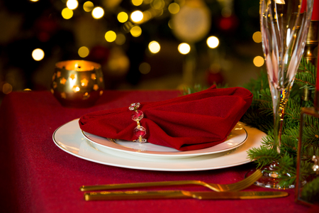 Beautiful served table with candles, Red tablecloth and napkins, white china, gold cutlery, crystal champagne glasses. Holiday setting, close-up plate, Christmas mood. Stock Photo - 114476070