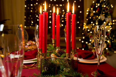 Beautiful served table with candles, Red tablecloth and napkins, white china, gold cutlery, crystal champagne glasses. Living room decorated with lights and Christmas tree. Holiday setting Stock Photo