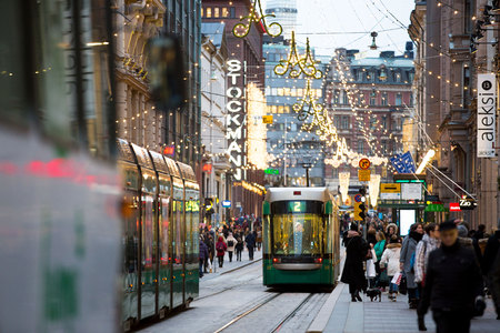HELSINKI, FINLAND - DEC 17, 2017: Bright trams on central streets in Helsinki during Christmas. A lot of people, holiday sales and bright decorations.  City decorated with Christmas lights