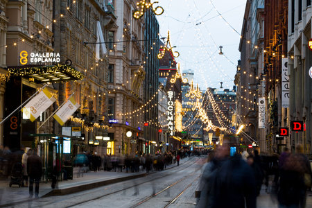 HELSINKI, FINLAND - DEC 17, 2017: Helsinki streets decorated with Christmas lights. A lot of people, holiday sales and bright decorations.