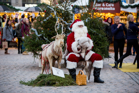 HELSINKI, FINLAND - DEC 17, 2017: Santa Claus sitting on square with reindeer in the centre of Helsinki at Christmas market