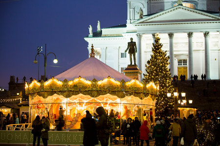 HELSINKI, FINLAND - DECEMBER 11, 2017: Traditional childrens rides carousel at Christmas holiday market on Senate Square opposite the Cathedral. Festive street with Christmas decorations