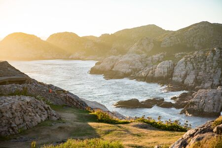 Serene Scandinavian summer landscape on south coast of Norway. Rocky Mountains, fjord from top. Sunset sky. Lindesnes
