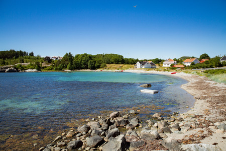 Serene scandinavian summer landscape of little village on south coast of Norway. Sunny sand and rocky beach with turquoise quiet water. 版權商用圖片