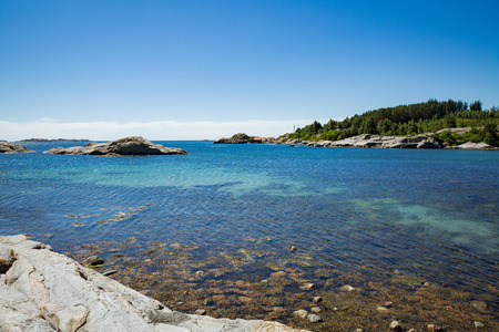 Serene scandinavian summer landscape on south coast of Norway. Sunny rocky beach with turquoise quiet water. Stock Photo