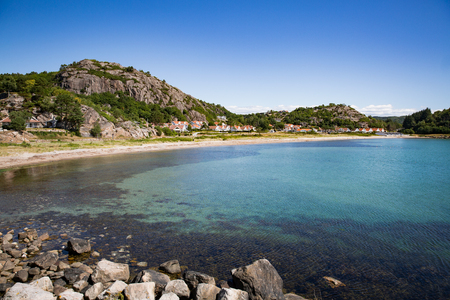 Serene scandinavian summer landscape of little village on south coast of Norway. Sunny sand and rocky beach with turquoise quiet water. 免版税图像
