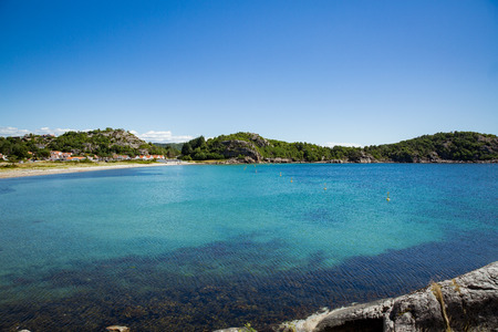 Serene scandinavian summer landscape of little village on south coast of Norway. Sunny sand and rocky beach with turquoise quiet water. Reklamní fotografie