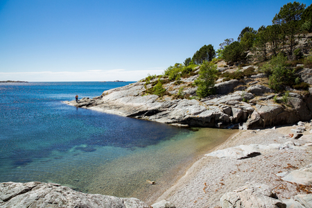 Serene scandinavian summer landscape on south coast of Norway. Sunny rocky beach with turquoise quiet water. 版權商用圖片