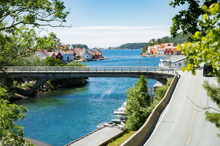 Peaceful rustic Scandinavian summer landscape. Small town on the south coast of Norway. Highway and bridge over fjord.