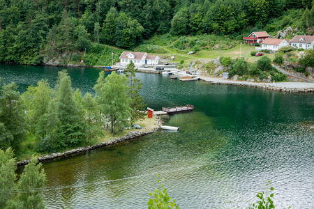 Serene scandinavian summer landscape of little village on south coast of Norway. Forest, mountains, emerald green quiet water. 版權商用圖片
