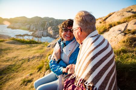 Liebevolles älteres Paar wandern, auf einer windigen Felsspitze sitzen, erkunden. Aktiver reifer Mann und Frau in Decke gehüllt, umarmt und glücklich lächelnd. Malerischer Blick auf Meer, Berge. Norwegen, Lindesnes. Standard-Bild