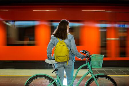 Teenager girl in jeans with yellow backpack and bike standing on metro station, waiting for train, smiling, laughing. Orange train passing by behind the girl. Futuristic subway station. Finland, Espoo Reklamní fotografie
