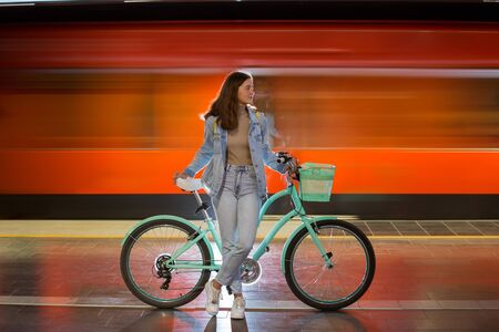 Teenager girl in jeans with yellow backpack and bike standing on metro station, waiting for train, smiling, laughing. Orange train passing by behind the girl. Futuristic subway station. Finland, Espoo Imagens