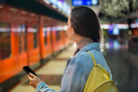 Ragazza adolescente in jeans con zaino in piedi sulla stazione della metropolitana tenendo in mano lo smartphone, scorrendo e mandando SMS, sorridendo e ridendo. Stazione della metropolitana luminosa futuristica. Finlandia, Espoo
