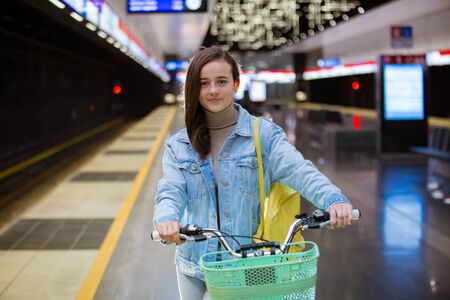 Teenager girl in jeans with yellow backpack and bike standing on metro station, waiting for train, smiling and laughing. Futuristic bright subway station. Finland, Espoo