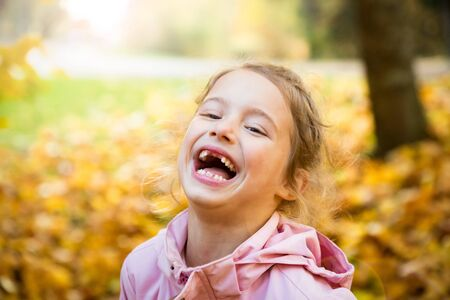 Portrait of Cute little girl with missing teeth playing with yellow fallen leaves in autumn forest. Happy child laughing and smiling. Sunny autumn forest, sun beam. 写真素材