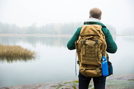 Mature man exploring Finland in the fall, looking into fog. Hiker with big backpack standing on mossy rock. Scandinavian landscape with misty sea and autumn forest. Back view