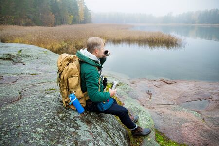 Mature man exploring Finland in the fall. Hiker with big backpack sit on mossy rock, drink hot coffee from flask. Scandinavian landscape with misty sea and autumn forest.