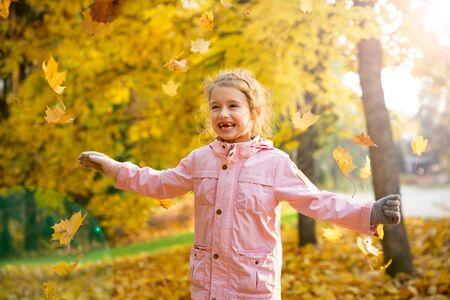 Śliczna mała dziewczynka z brakującymi zębami bawi się żółtymi opadłymi liśćmi w jesiennym lesie. Szczęśliwe dziecko śmiejąc się i uśmiechając. Słoneczny jesienny las, promień słońca.