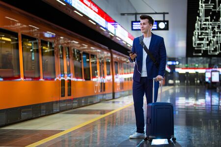 Young stylish handsome man in suit with suitcase standing on metro station holding smart phone in hand, scrolling and texting, smiling and laughing. Orange train passing by. Futuristic bright subway