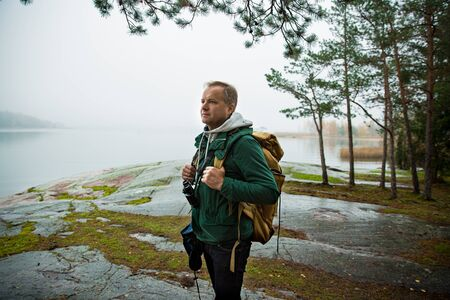 Mature man exploring Finland in the fall, looking into fog. Hiker with big backpack standing on mossy rock. Scandinavian landscape with misty sea and autumn forest.