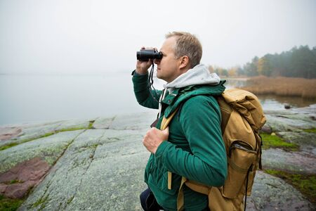Mature man exploring Finland in the fall, looking into fog through binoculars. Hiker with big backpack standing on mossy rock. Scandinavian landscape with misty sea and autumn forest. 写真素材
